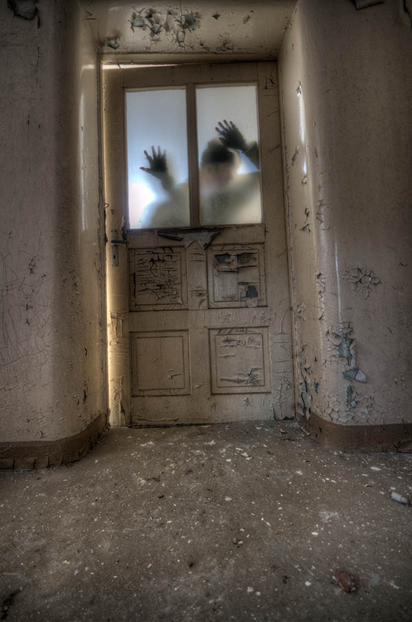 cryptic photo of a being behind a door in an old asylum in Berlin by Nathan Wright on Unsplash